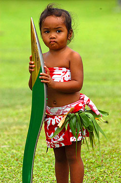 The relay continues in the Cook Islands. Dressed in island clothes, a local girl is bemused by the attention created by the baton's visit.